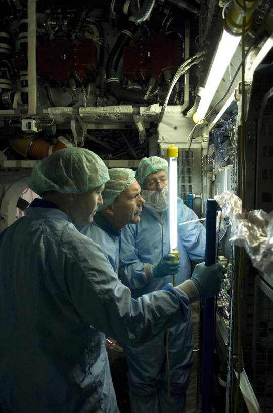 ESA astronaut Hans Schlegel inspects a payload rack inside the European Columbus laboratory. Credits: ESA - S. Corvaja