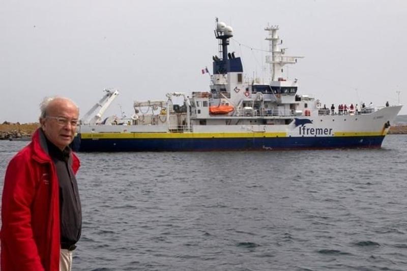 Bernard Decré devant le Suroit, le navire de l'Ifremer, lors de la campagne de recherches en juillet 2011. Crédits : Association La recherche de l'Oiseau Blanc.