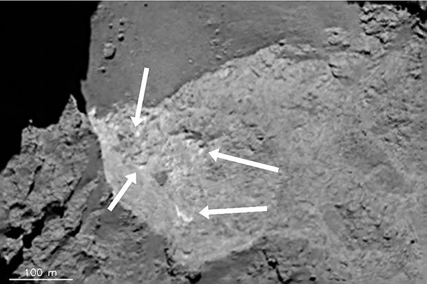 Les petites zones claires indiquées par les flèches mesurent moins de 10 m de côté et révèlent probablement de la glace d'eau. Image prise par OSIRIS-NAC le 7 août 2014. Crédits : ESA/Rosetta/MPS for OSIRIS Team MPS/UPD/LAM/IAA/SSO/INTA/UPM/...